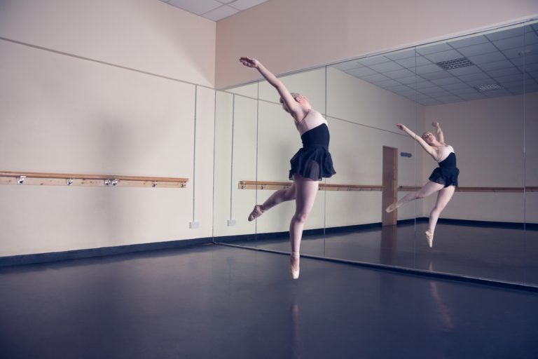 a ballet dancer infront of a mirror dancing in a commercial space